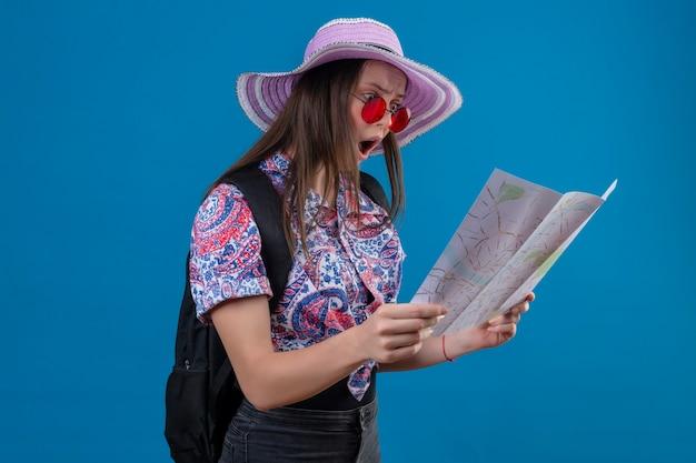Jonge reizigersvrouw in zomerhoed die rode zonnebril draagt die kaart houdt die ernaar kijkt verbaasd en verrast met brede open mond die zich over blauwe achtergrond bevindt