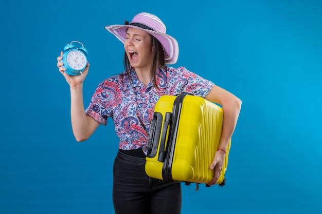 Jonge reizigersvrouw in zomerhoed die zich met gele koffer bevinden die wekker houden geïrriteerd en gefrustreerd schreeuwen van woede over blauwe achtergrond
