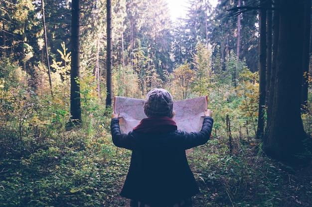 Jonge reizigersvrouw met kaart, bij de herfst groen bos in zonnige dag.