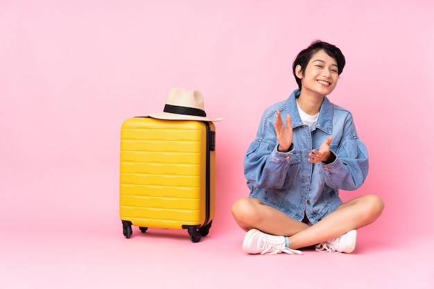 Jonge reizigersvrouw met kofferzitting op de vloer over geïsoleerd roze toejuichen na presentatie in een conferentie