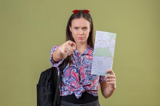 Jonge reizigersvrouw met rode zonnebril op hoofd en met de ontevreden kaart van de rugzakholding het richten aan camera met vinger met boze uitdrukking over groene muur