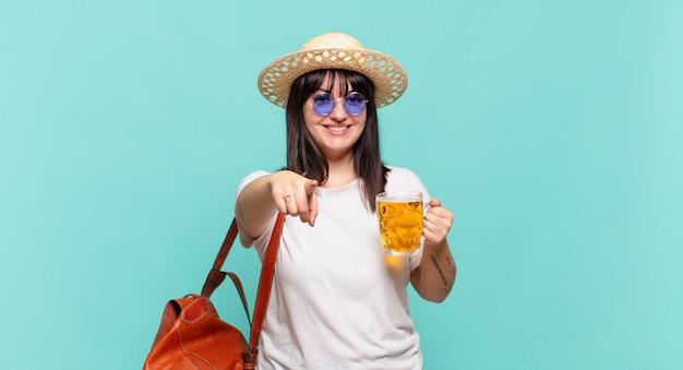 Jonge reizigersvrouw wijzend op camera met een tevreden, zelfverzekerde, vriendelijke glimlach, die jou kiest