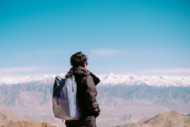 Jonge reizigerswandelaar met rugzak op piek van sneeuwberg op khardung la, hoogste berijdbare weg in leh, ladakh, india. reis en toerisme concept