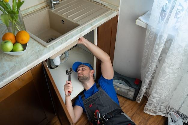 Jonge reparateur met gereedschap in zijn handen en een blauwe dop is de gootsteen in de keuken aan het repareren