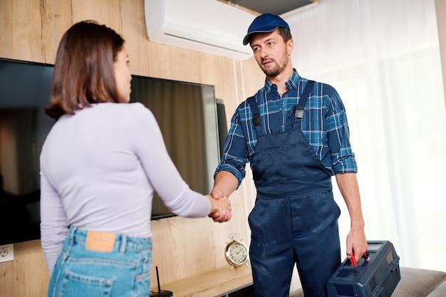 Jonge reparateur van onderhoudsdienst schudden hand van huisvrouw na reparatie van plasmapaneel