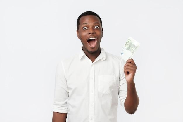 Jonge rijke afro-amerikaanse man in shirt met honderd euro met verbazing
