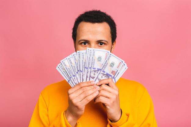 Jonge rijke gelukkig man in casual holdingsgeld dollarbiljetten met verrassing geïsoleerd over roze muur