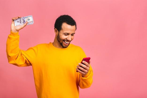 Jonge rijke man in casual holdingsgeld dollarbiljetten en mobiele telefoon met verrassing geïsoleerd over roze muur