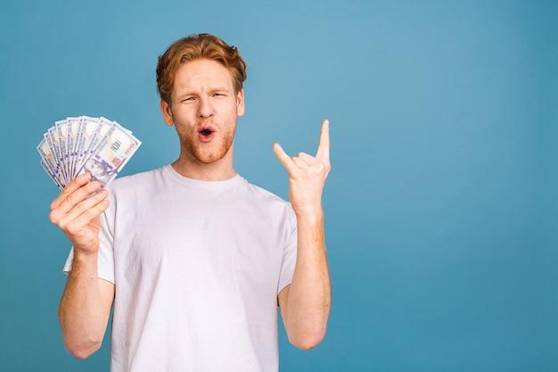 Jonge rijke roodharige man in casual geld dollarbiljetten met verrassing