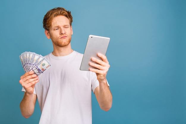 Jonge rijke roodharige man in casual geld dollarbiljetten met verrassing Premium Foto