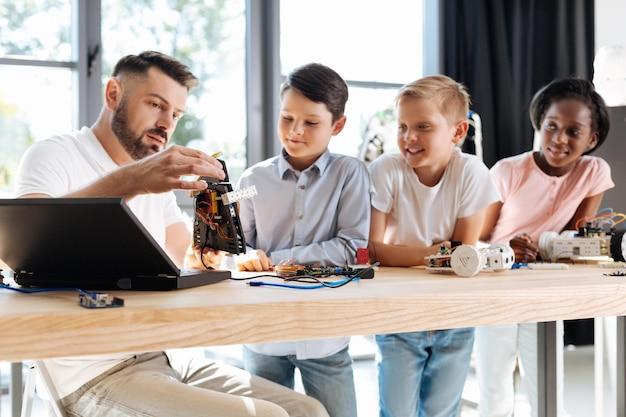 Jonge robotica-leraar zit aan de tafel met zijn studenten
