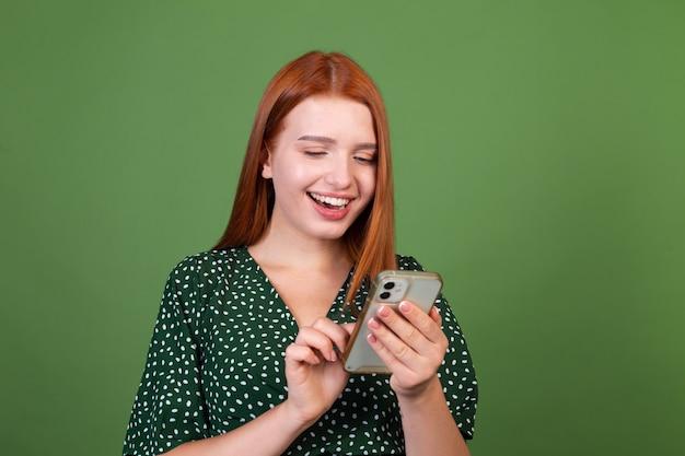 Jonge rode haarvrouw op groene muur met mobiele telefoon gelukkig positief opgewonden