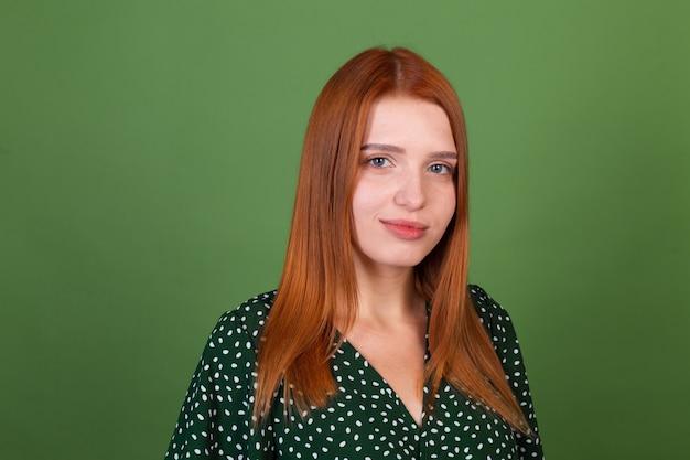 Jonge rode haarvrouw op groene muur met zelfverzekerde glimlach