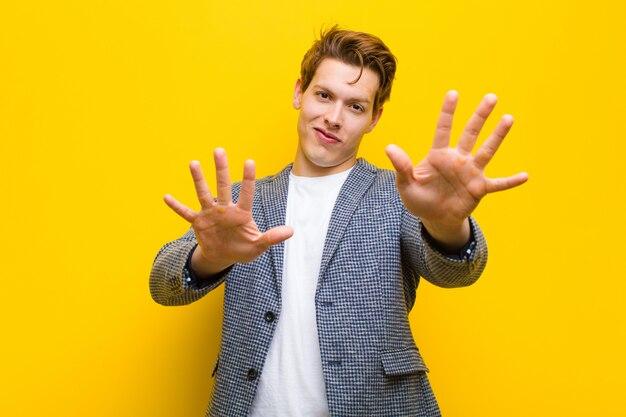 Jonge rode hoofd en mens die vriendschappelijk glimlachen kijken, die nummer tien of tiende met vooruit hand tonen, die tegen oranje achtergrond aftellen