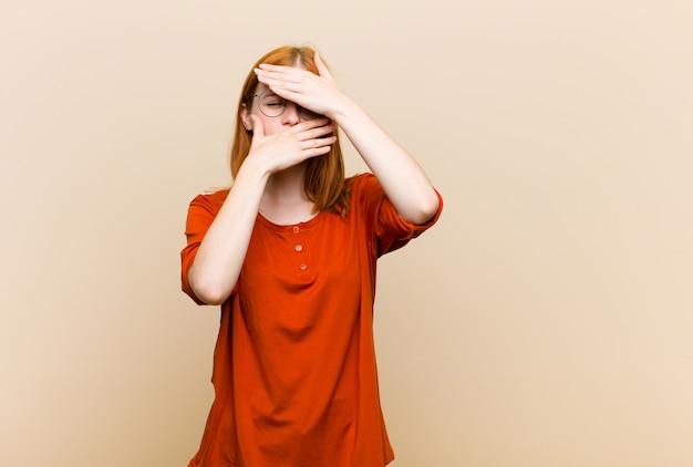 Jonge rode hoofd mooie vrouw die gezicht behandelt met beide handen die nee zeggen tegen de camera! afbeeldingen weigeren of foto's verbieden