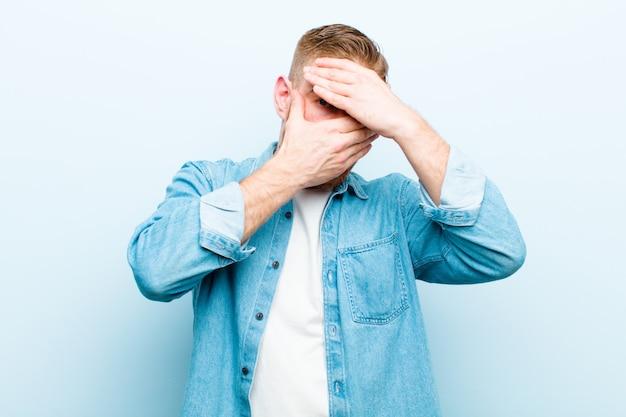 Jonge rode hoofdmens die gezicht bedekt met beide handen die nee tegen de camera zegt! afbeeldingen weigeren of foto's verbieden tegen een zachtblauwe achtergrond