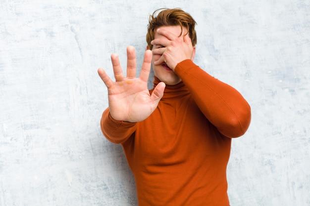 Jonge rode hoofdmens die gezicht behandelt met hand en andere hand vooraan zet