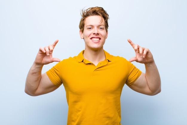 Jonge rode hoofdmens die of eigen glimlach met beide handen ontwerpen schetsen, die positief en gelukkig, wellnessconcept kijken over blauwe muur