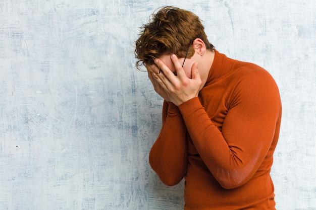 Jonge rode hoofdmens die ogen behandelen met handen met een droevige, gefrustreerde blik van wanhoop, huilend, zijaanzicht over grungemuur