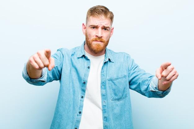 Jonge rode hoofdmens die op camera met beide vingers en boze uitdrukking vooruit wijzen, die u vertellen om uw plicht te doen