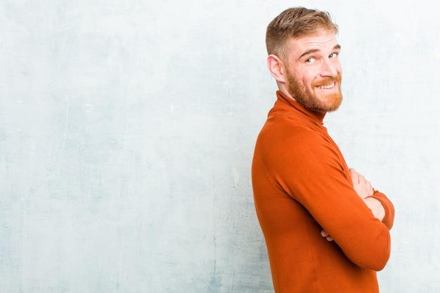 Jonge rode hoofdmens die schildpadhals draagt die vrolijk glimlacht, zich gelukkig, tevreden en ontspannen voelt, met gekruiste armen en kijkend aan de kant tegen concrete muur