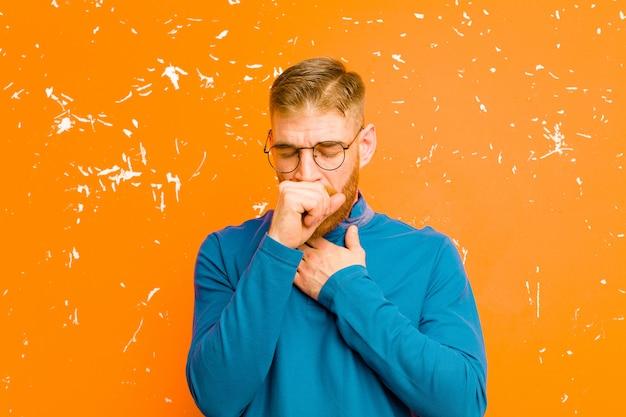 Jonge rode hoofdmens die ziek met keelpijn en griepsymptomen voelt, hoestend met mond die over grunge oranje muur wordt behandeld