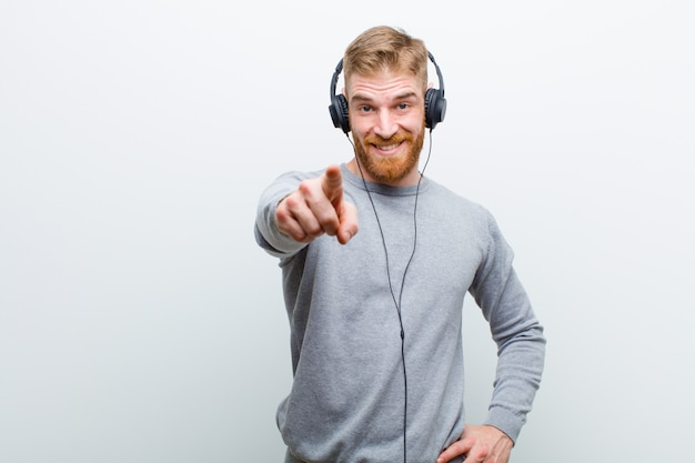 Jonge rode hoofdmens het luisteren muziek met hoofdtelefoons