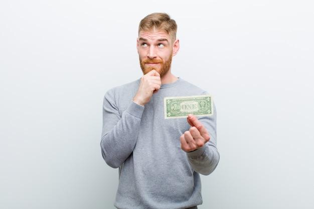 Jonge rode hoofdmens met dollars tegen witte achtergrond