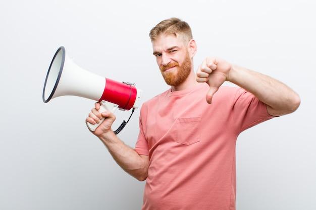 Jonge rode hoofdmens met een megafoon tegen wit