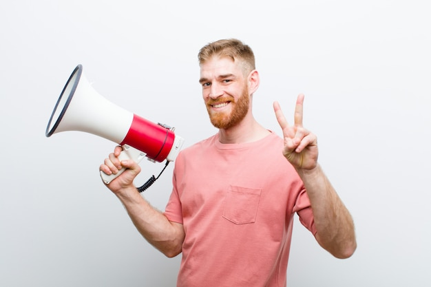 Jonge rode hoofdmens met een megafoon