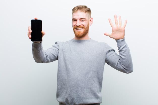 Jonge rode hoofdmens met een slimme telefoon tegen witte achtergrond