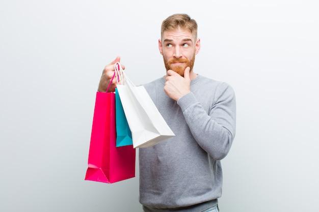 Jonge rode hoofdmens met het winkelen zakken