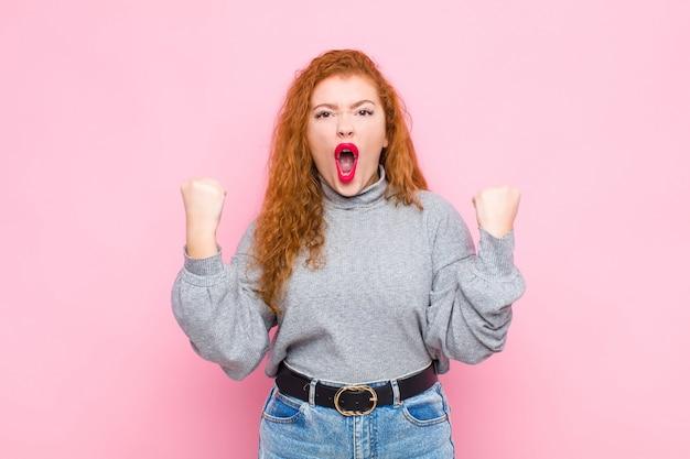 Jonge rode hoofdvrouw die agressief met een boze uitdrukking of met gebalde vuisten het vieren succes tegen roze muur agressief schreeuwt