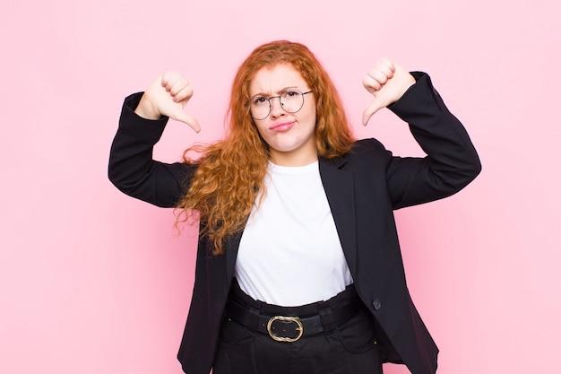 Jonge rode hoofdvrouw die droevig, teleurgesteld of boos kijkt, die duimen neer in onenigheid tonen, gefrustreerd over roze muur voelen