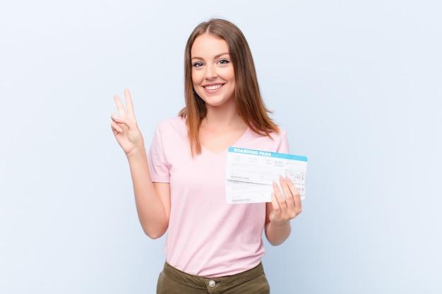 Jonge rode hoofdvrouw tegen vlakke muur met de kaartjes van de vliegtuig instapkaart