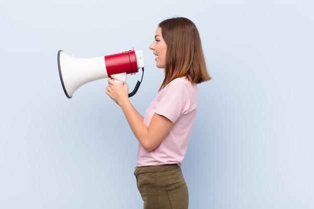 Jonge rode hoofdvrouw tegen vlakke muur met een megafoon