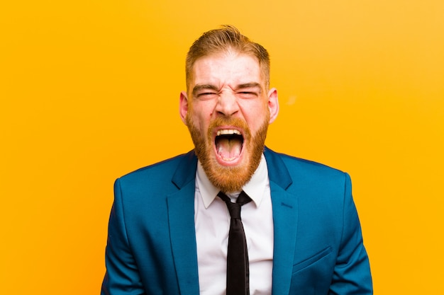 Jonge rode hoofdzakenman die agressief schreeuwt, kijkend zeer boos, gefrustreerd, verontwaardigd of geïrriteerd, schreeuwend nr tegen oranje achtergrond