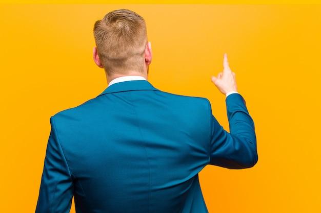 Jonge rode hoofdzakenman die en zich op voorwerp op exemplaar ruimte bevinden richten, achtermening tegen sinaasappel