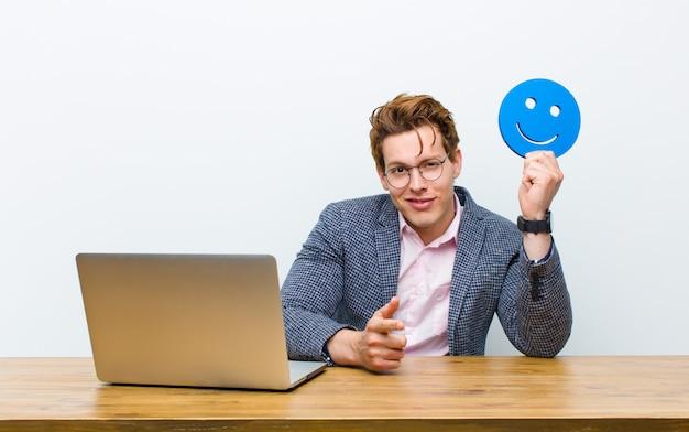 Jonge rode hoofdzakenman die in zijn bureau met een het glimlachen gezichtspictogram werkt