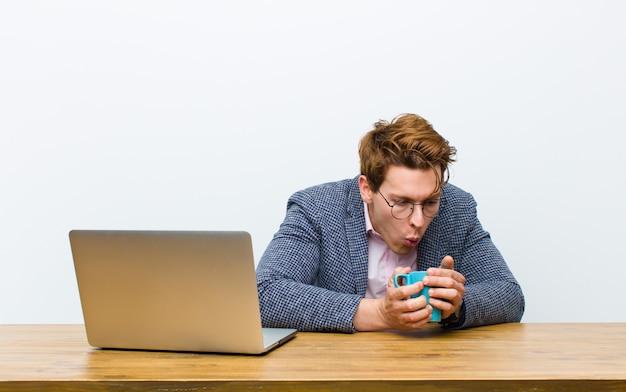 Jonge rode hoofdzakenman die in zijn bureau met een hete koffiekop werkt