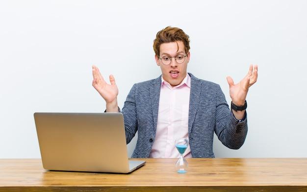 Jonge rode hoofdzakenman die in zijn bureau met een klok werkt. tijd concept