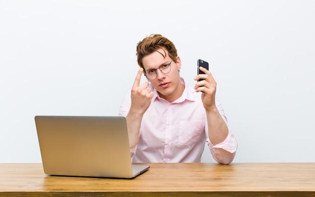 Jonge rode hoofdzakenman die in zijn bureau met een monile telefoon werkt