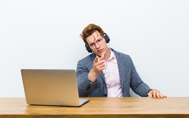 Jonge rode hoofdzakenman die in zijn bureau met hoofdtelefoons werkt