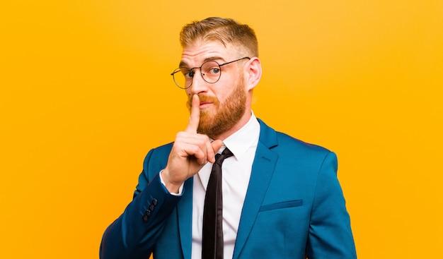 Jonge rode hoofdzakenman die om stilte en stil vragen, gebaren met vinger voor mond, shh zeggen of een geheim houden tegen sinaasappel