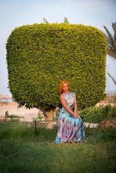 Jonge rode vrouw op een bankje