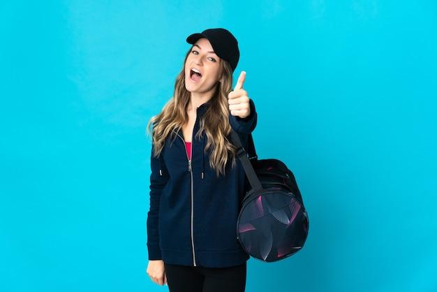 Jonge roemeense sportvrouw met sporttas die op blauwe muur met omhoog duimen wordt geïsoleerd omdat er iets goeds is gebeurd