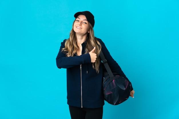 Jonge roemeense sportvrouw met sporttas die op blauwe muur wordt geïsoleerd die duimen op gebaar geeft
