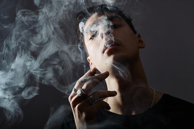 Jonge rokende man op zwart