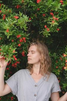 Jonge romantische dame die van bloesem van bloemen geniet