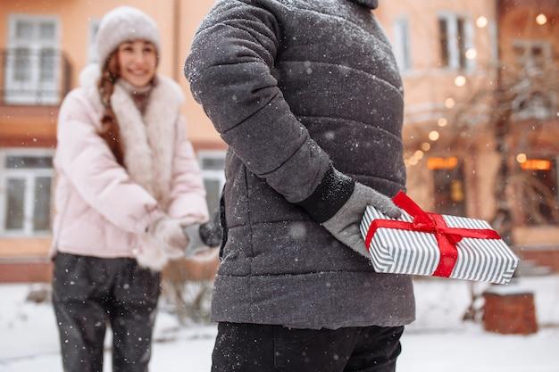 Jonge romantische man staat op het punt een cadeau te geven aan zijn vriendin voor valentijnsdag. mannetje met een geschenkdoos met een rode strik achter zijn rug op een besneeuwde winterdag.